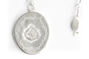 "Patricia Sullivan: ""Widget Locket #5: Homage to Vanity"" (front detail and clasp).  Chased sterling silver, archival paper, Plexiglas, sterling chain/clasp. 19  7/8"" x 2  5/16"" x 5/16"", 2014. Photo: P. Sullivan"