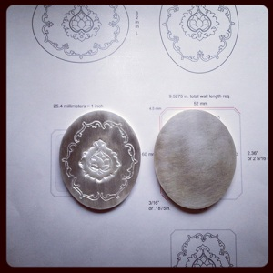 Preparatory drawings in Illustrator and work-in-progress halves of the metal locket in early stages of fabrication. Photo: P. Sullivan