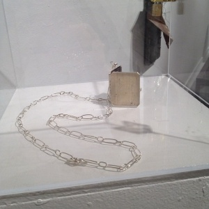 "Patricia Sullivan: ""Widget Locket No. 2"" (installation view). Sterling silver (fabricated), fabric, archival paper, Plexiglas, handmade silver chain/hinge/clasp, 20.75"" x 1.75"" x .25"", 2013. Photo: P.Sullivan"